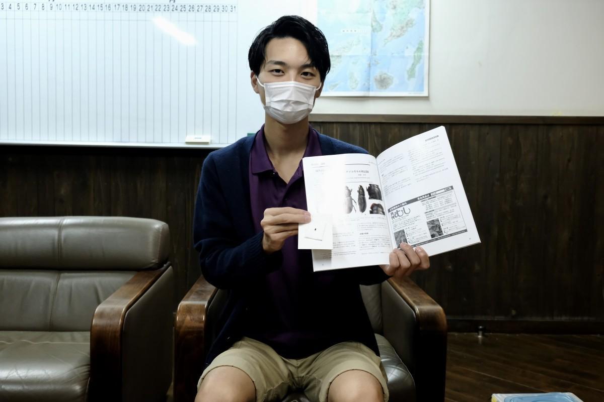 「月刊むし」とヤエヤマニセツツマグソコガネの標本を手にする渡邉さん