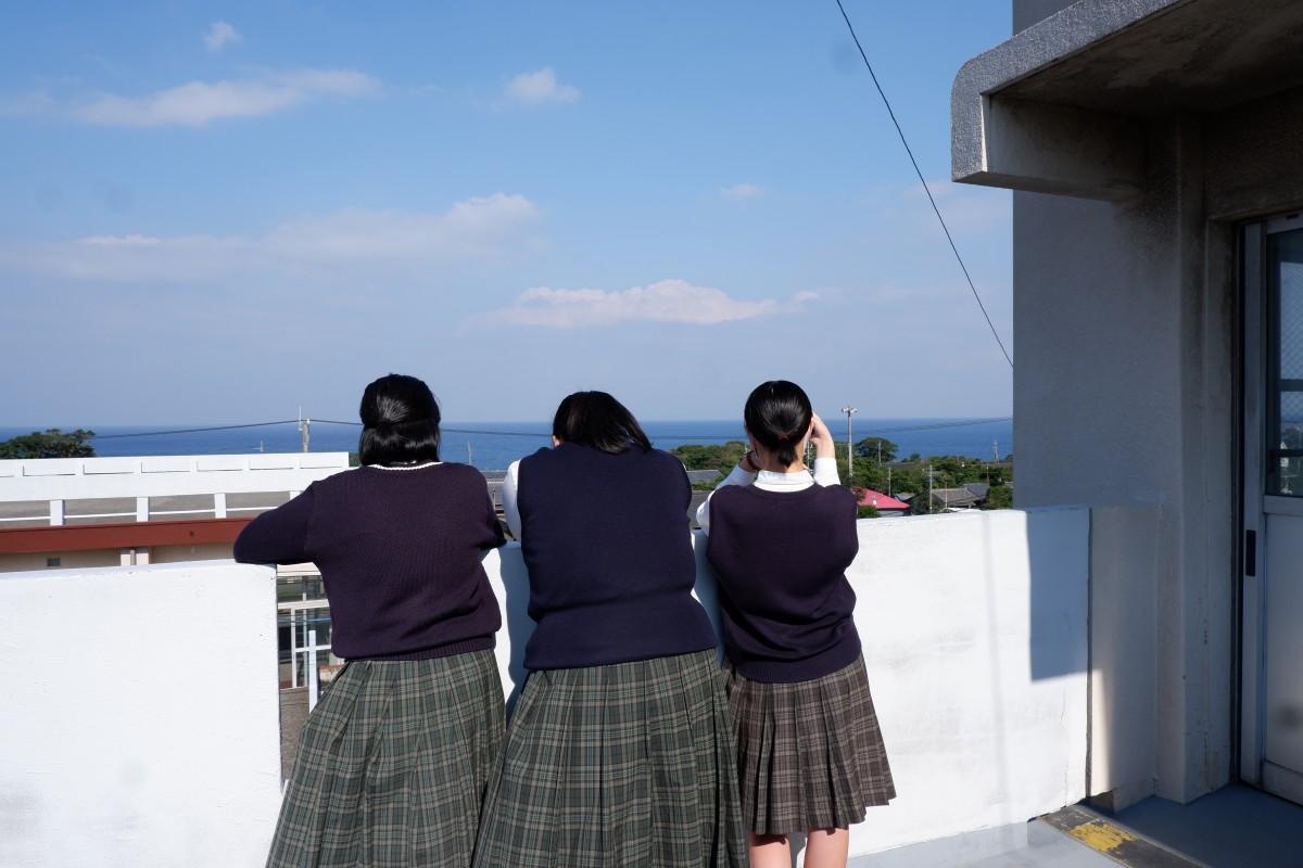 屋久島高校の渡り廊下で「まつばんだ」の試験放送を聴く、吹奏楽部の3人