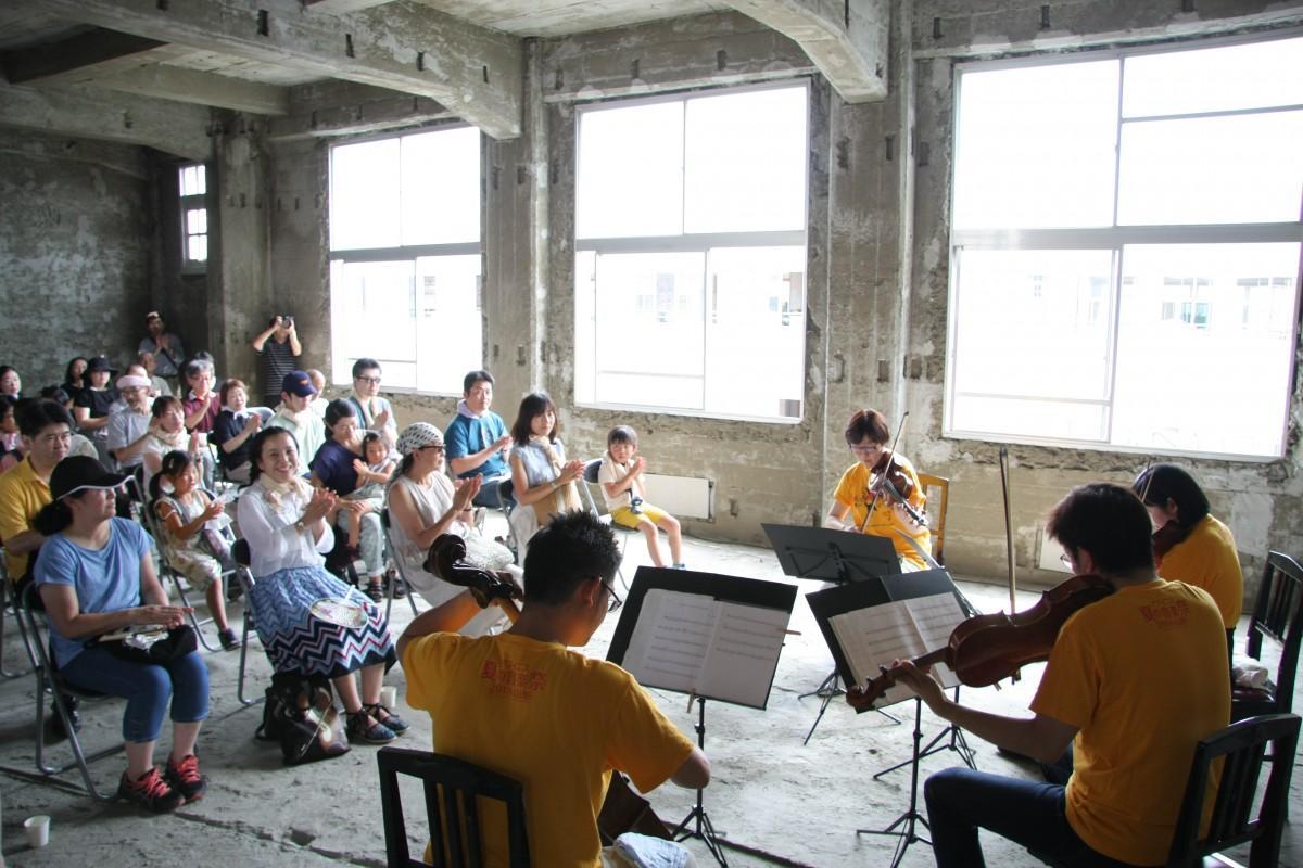 コンクリート打ち放し教室でクラシック音楽に耳を傾ける観客