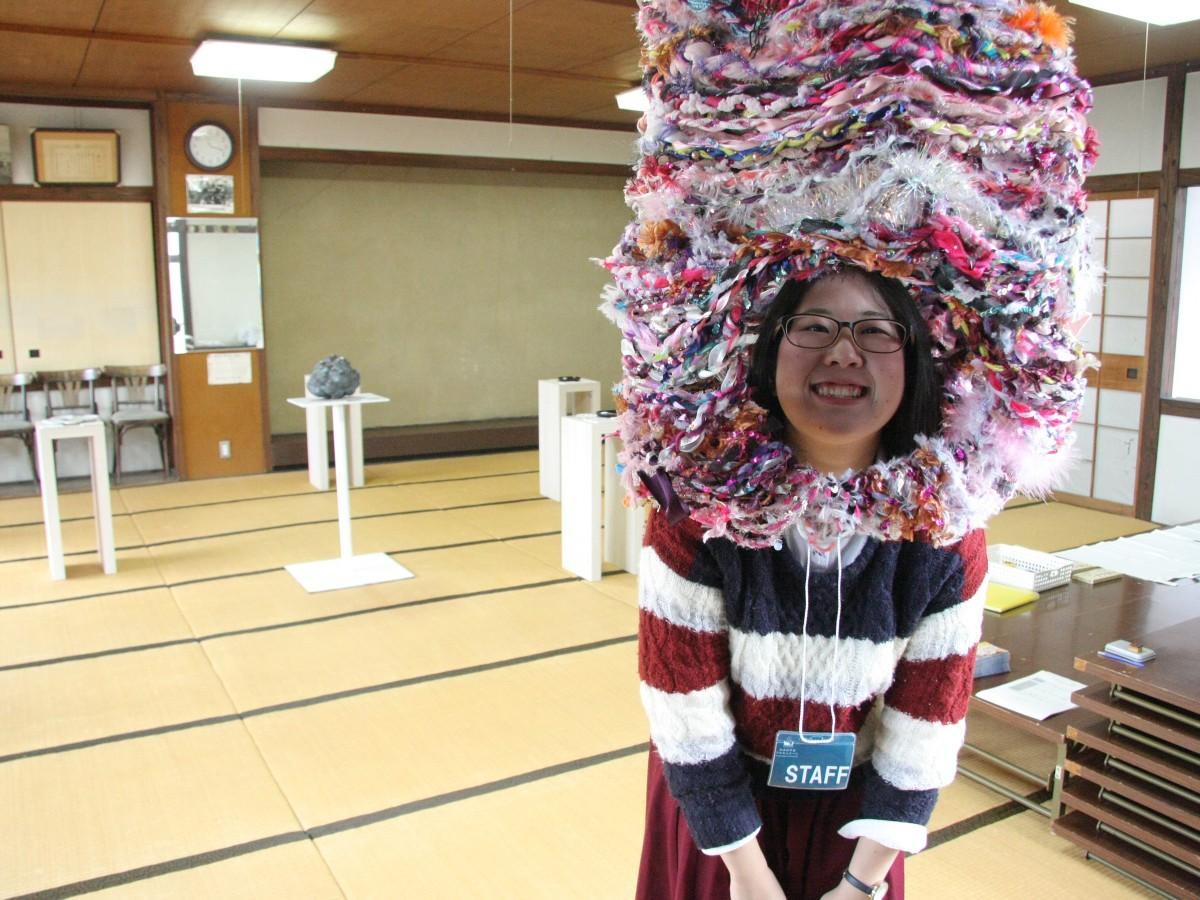 稲井佑羽さんの作品「ゆうあいちゃん」をかぶる「かまのやまフロエンナーレ」企画者の坂本彩奈さん