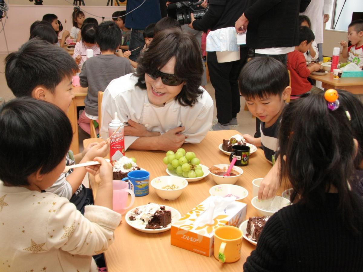ガトーショコラを食べる園児らと話す龍玄さん