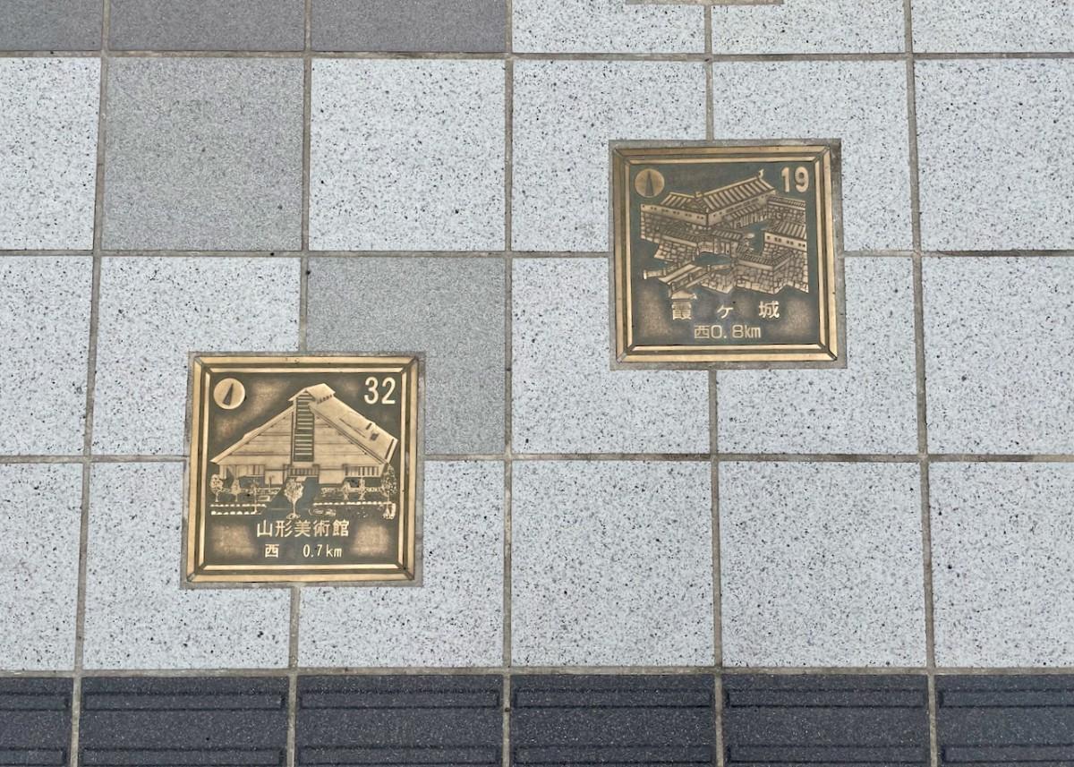 右上にナンバリングされた県内の観光地が描かれたブロンズ案内板