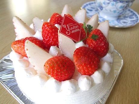 カットされた白いイチゴと赤いイチゴで彩られたデコレーションケーキ