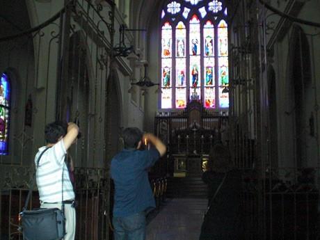 大聖堂のステンドグラスにカメラをむける参加者