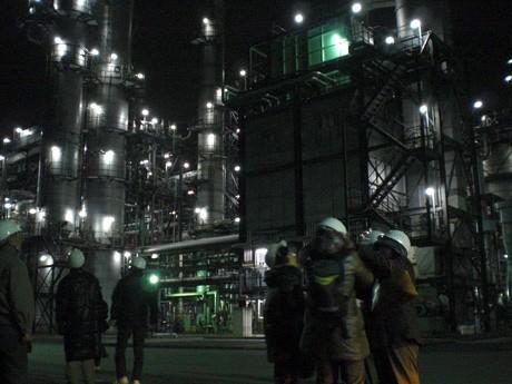 夜間照明に照らされる西部石油のプラントに「萌える」参加者