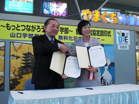 笑顔で協定書を交わす渡辺純忠山口市長(左)と久保田后子宇部市長