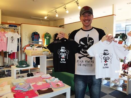同店でデザインしたオリジナルTシャツを手にする同店の濱田さん