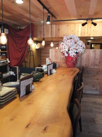 木の一枚板と白熱灯を施したカウンター席