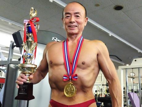 金メダルを首に掛け、優勝トロフィーを手に笑顔を見せる矢田部さん