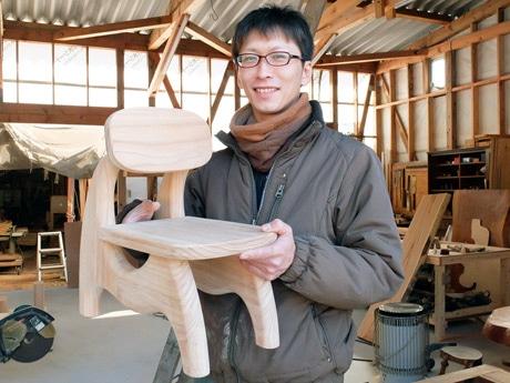 制作途中の椅子を抱える鮎川さん