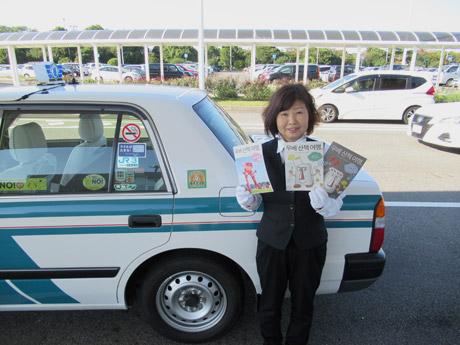 韓国語で書かれたリーフレットを持つ認定ドライバーの前田節子さん