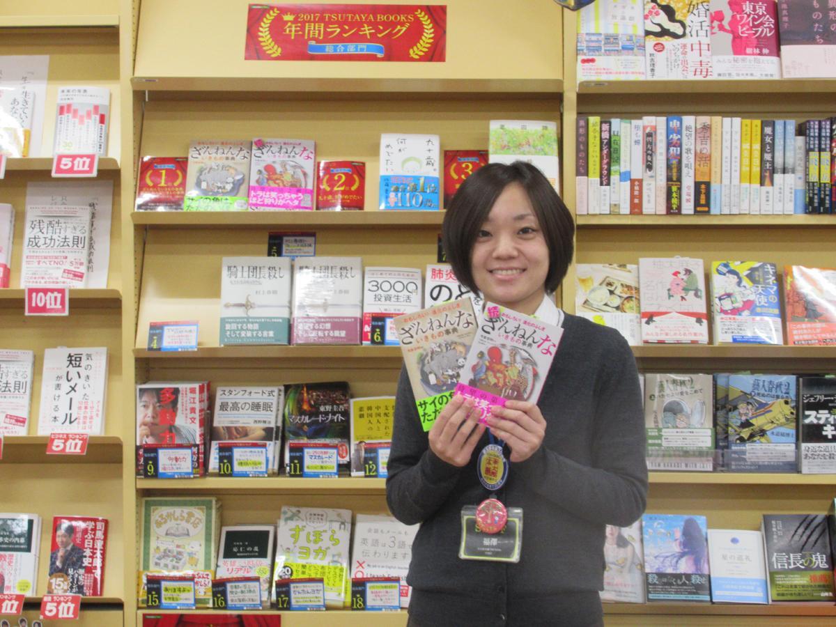 年間ランキングの棚を背にランキング1位の書籍を持つ福澤さん