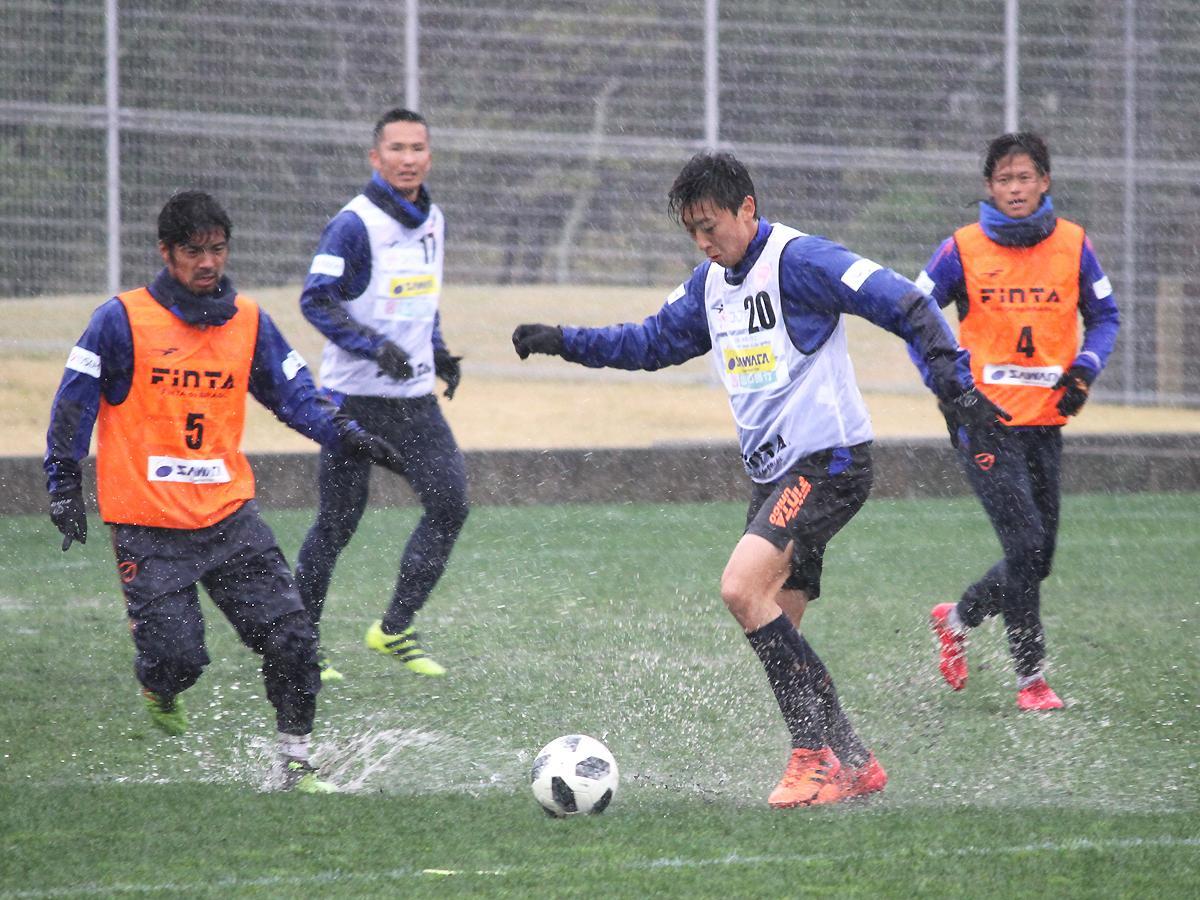 どしゃ降りの雨に打たれながら、練習する選手たち(19日の様子)