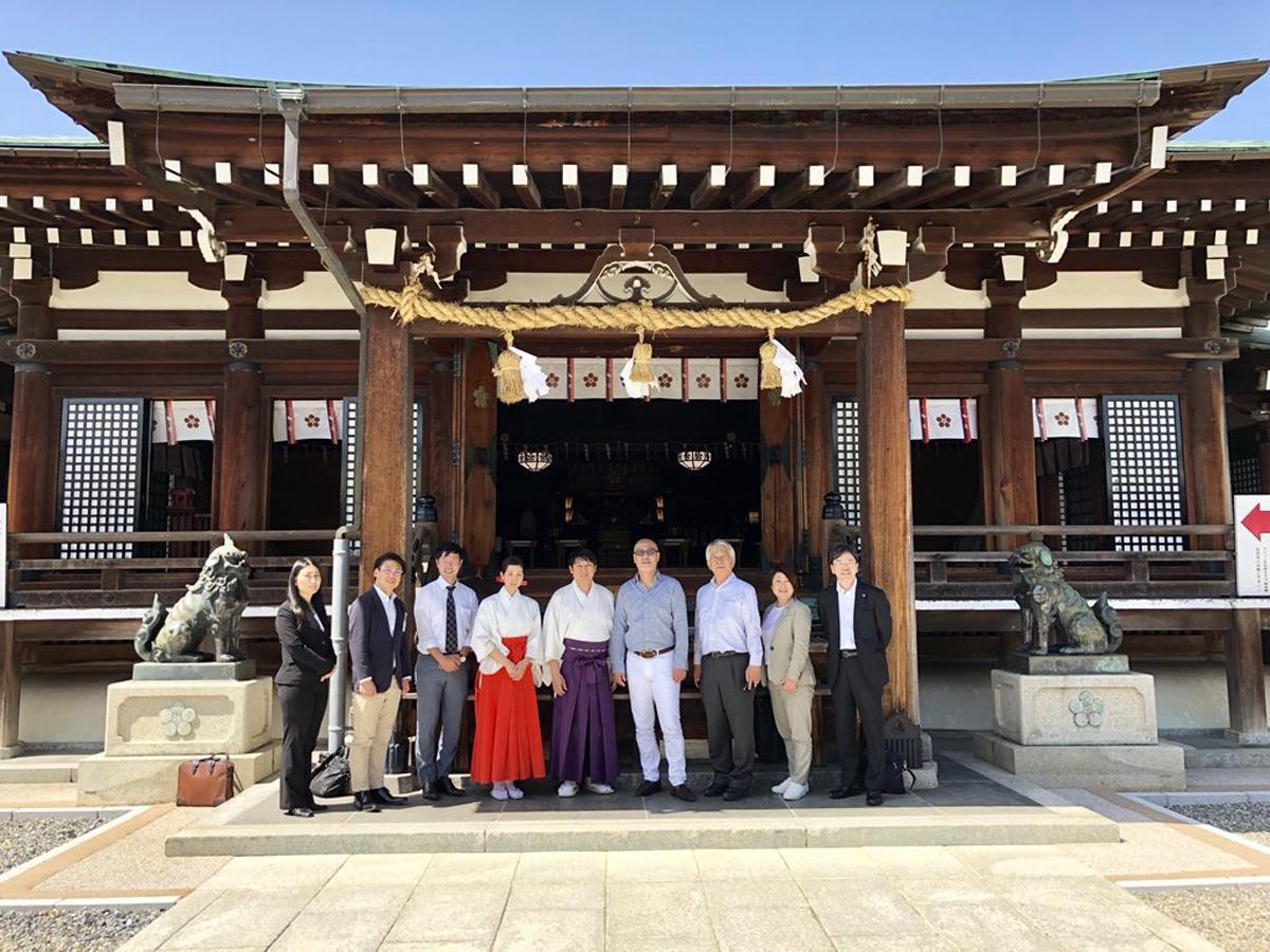 防府天満宮で下見を行う野澤孝智さん(右から4番目)やJAL山口支店社員ら