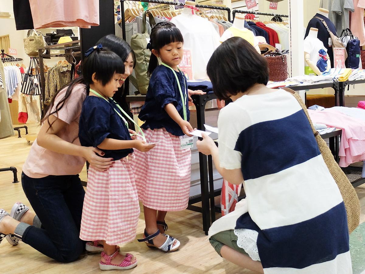 来店客に名刺を渡す「こども店長」の西七海ちゃん、心海ちゃん姉妹