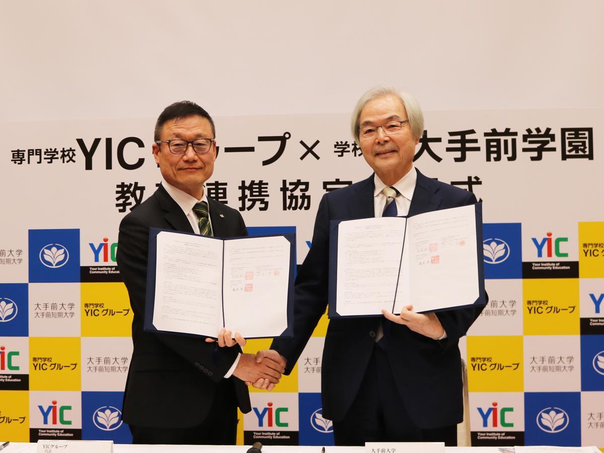 協定書を手に握手を交わすYICグループの井本理事長(左)と大手前大学の鳥越学長