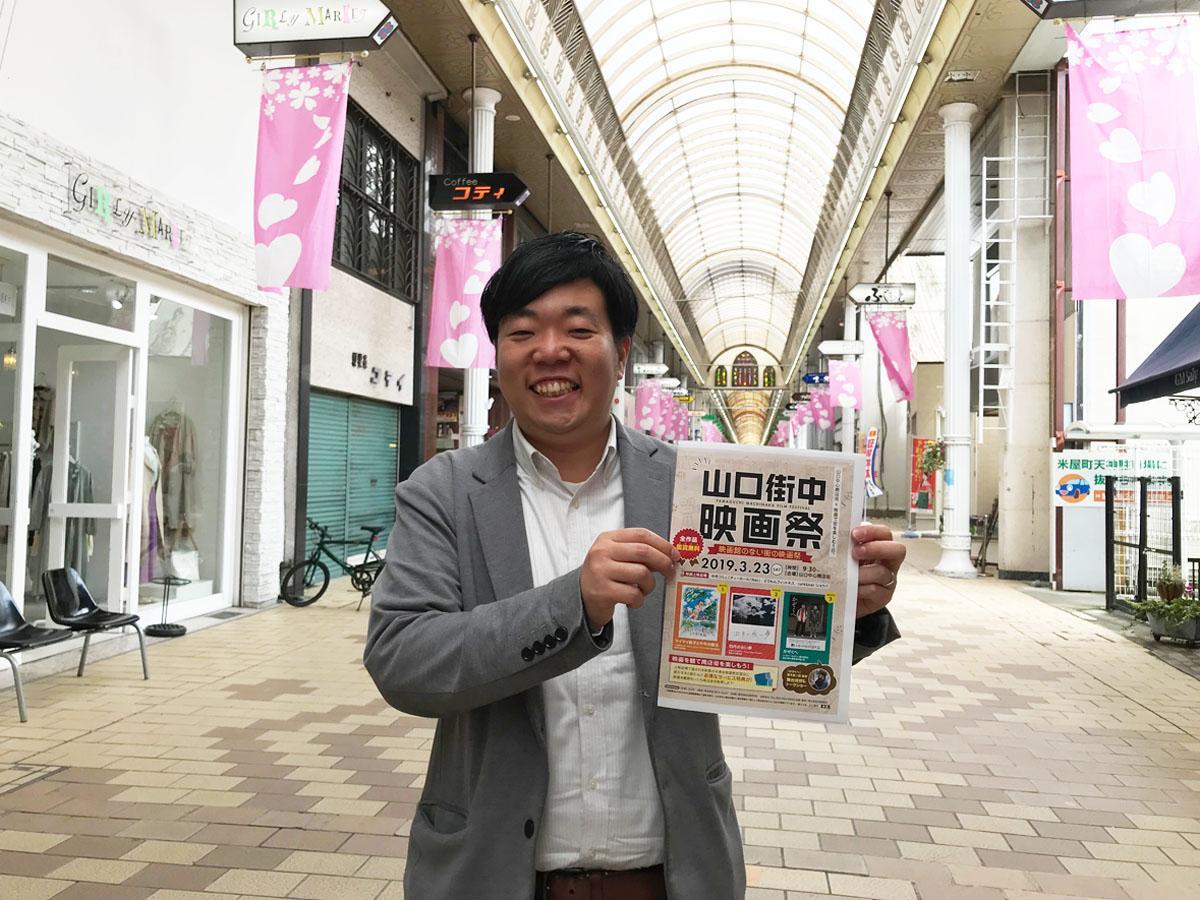 会場の商店街でイベントをPRする企画担当の石川さん