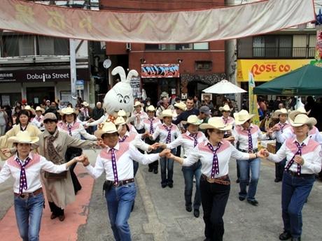 どぶ板通りをパレードする市民活動のマスコット「のたろん」と横須賀カントリーダンス・チーム
