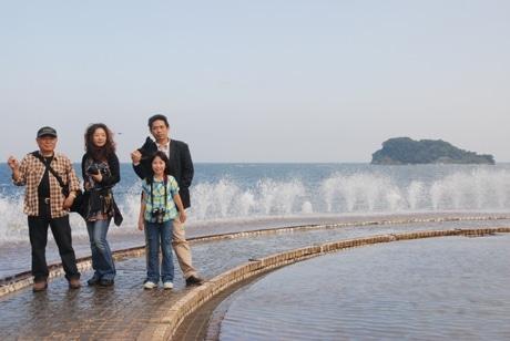 猿島をバックに、父親・長女・長男・孫が集まった小島さん一家のスナップ写真