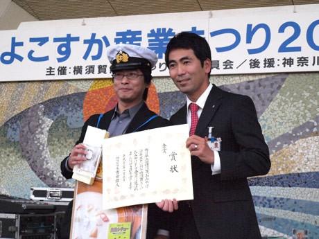 第2回横須賀おみやげコンテストで「黒船シチュー」(調味商事)が金賞を受賞。海軍帽子をかぶって出場した調味商事の瀬戸明さん(左)、吉田雄人・横須賀市長と