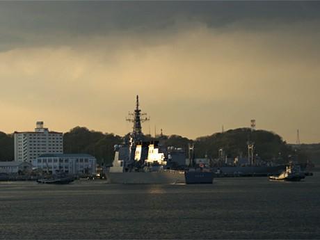 3月11日17時過ぎ、黒い雲に包まれた横須賀本港。夕日を照り返しながら海自イージス艦「きりしま」が被災地へ向かって出港。(写真撮影=dybrristol:mika)