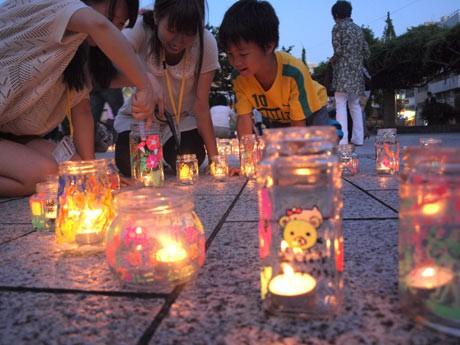 市内の小学生たちがガラス瓶に絵を描き、エコ・キャンドルに火をともした