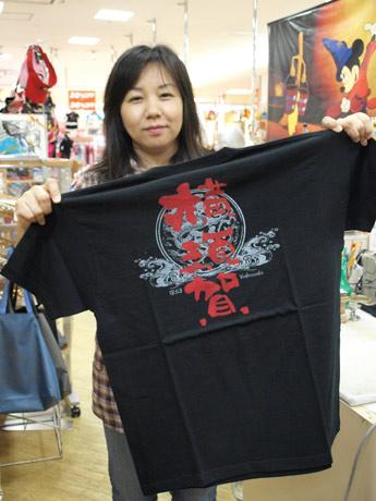 スカジャン柄Tシャツ「スカティ」を持つMCハウス専務の笹井さん