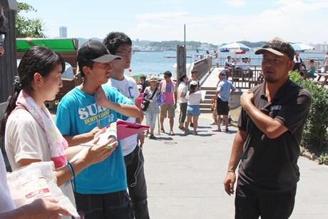 猿島で働くスタッフに取材する高校生記者たち