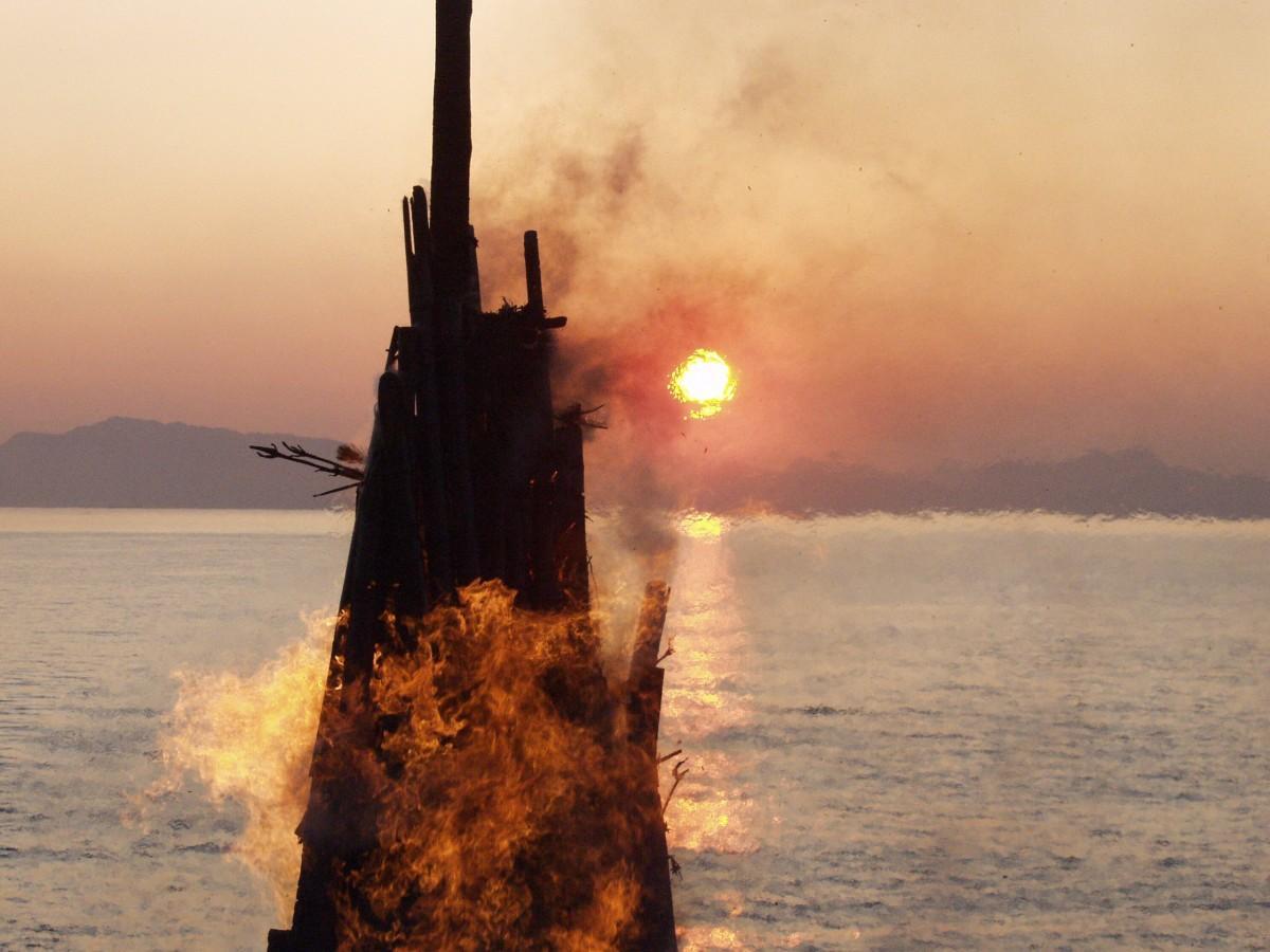 朝日とともに勢いよくも燃え上がる「おんべ焼き」(野比海岸)