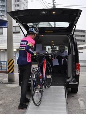 スロープを使ってタクシー車内に入れ、シートベルトで自転車を固定する