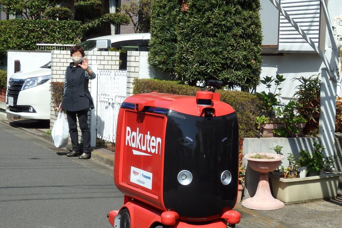 横須賀の馬堀海岸2丁目で、買い物利用者に見送られて公道を走る自動配送ロボット