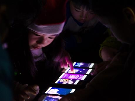 スマートフォンを並べて音楽を楽しむ音楽イベントの参加者