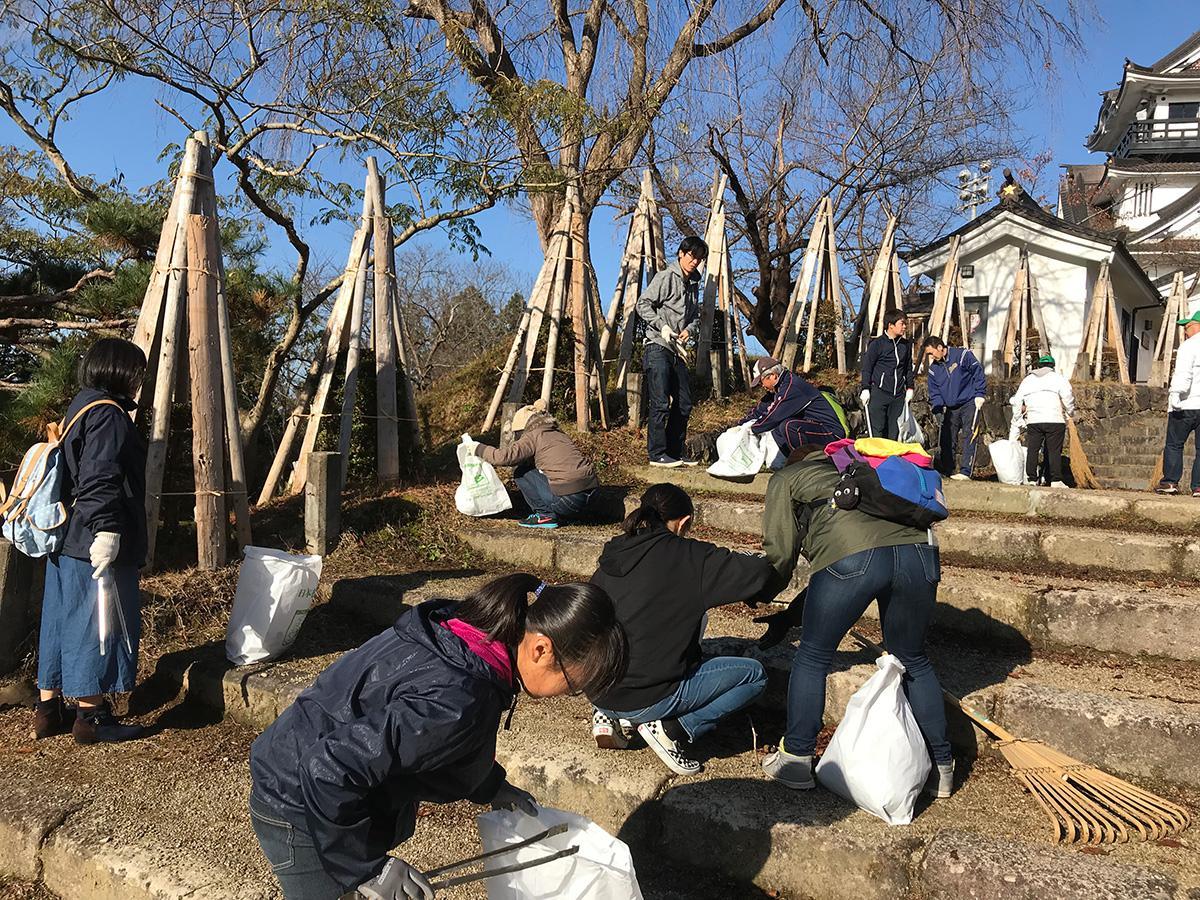 横手城址公園の落ち葉を拾い集めるボランティア参加者