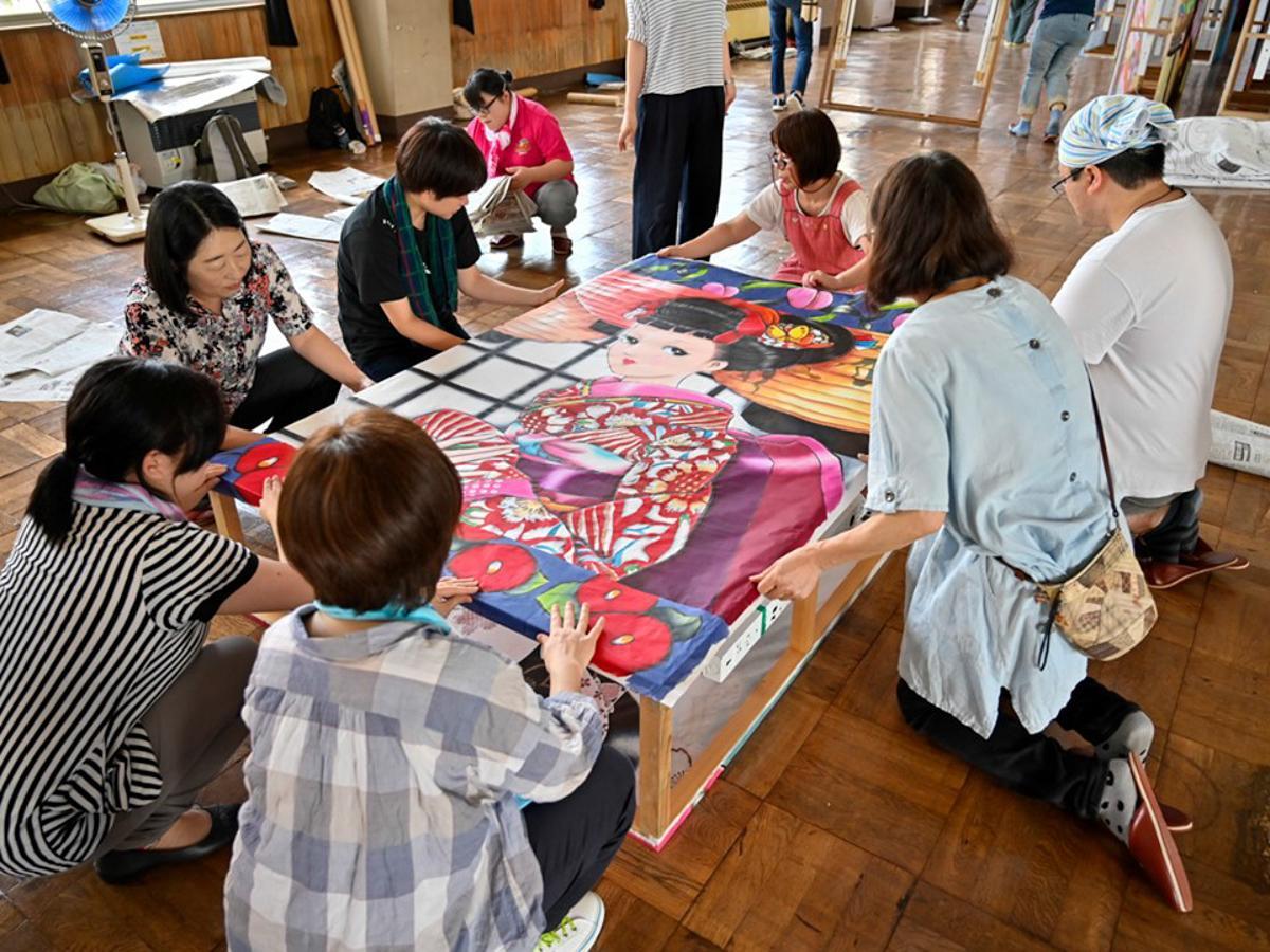 湯沢市で開かれた「絵どうろう」貼り付け作業の様子