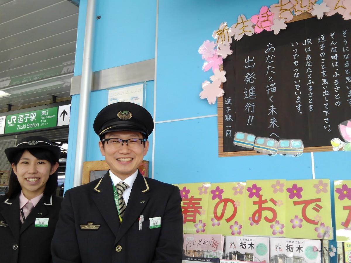 改札横の案内スペースに掲示された手作りのメッセージと、これを企画制作した駅員、熊倉さんと嶋貫さん