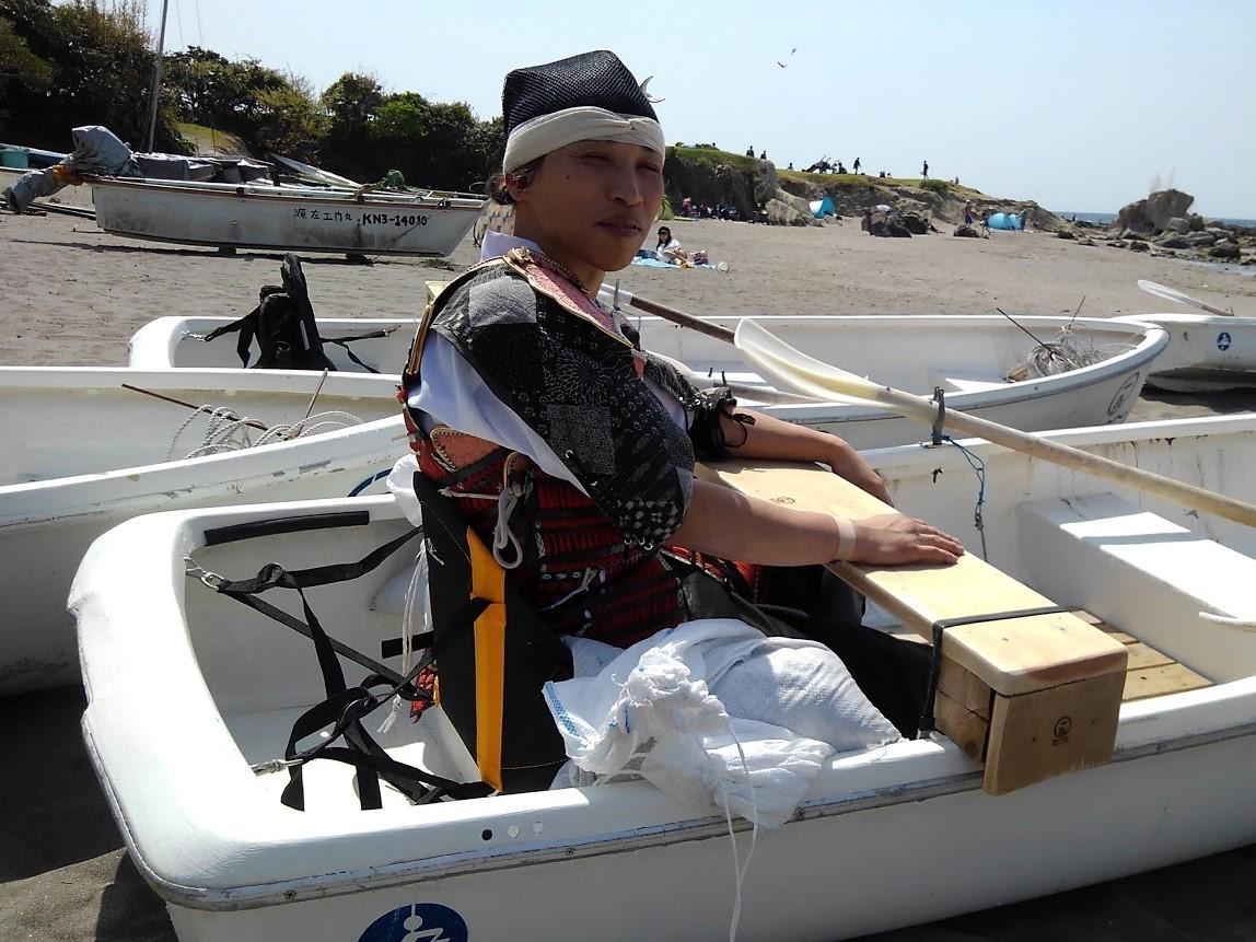 障がい者用に身体を固定できるよう工夫されたボートのシートに座ってみる主催者の一人、高野さん