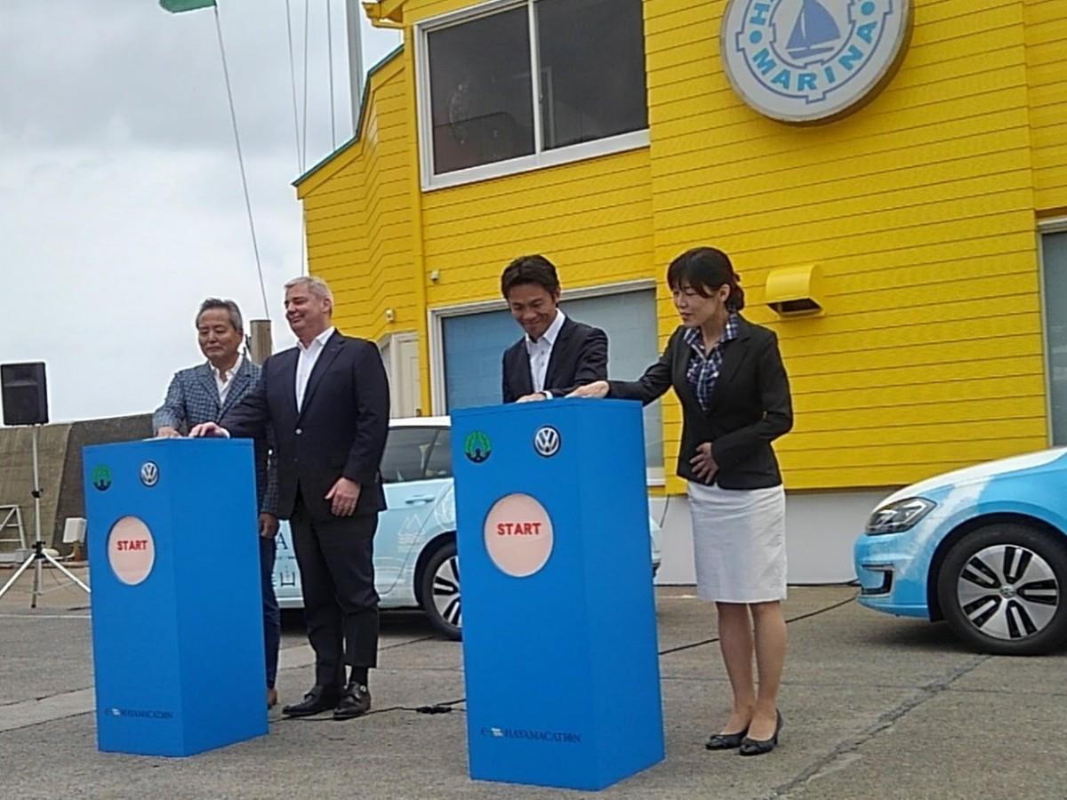 葉山マリーナで行われたプロジェクトキックオフセレモニーで点灯ボタンを押すVGJ 代表取締役社長 ティルシェアさん(左から2番目)と山梨崇仁町長(右から2番目)