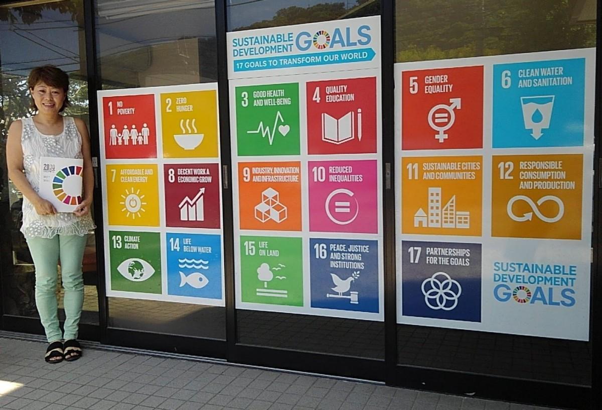 「HAYAMA GLOBAL」の代表、李由紀さん。17の目標が描かれたステッカーを掲示している事務所の前で