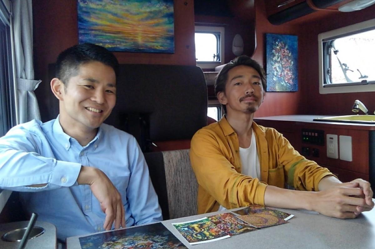 レンタルキャンピングカー内で、代表の櫻井謙さんと画家の本間亮次さん。展示の絵は、本間さんの作品