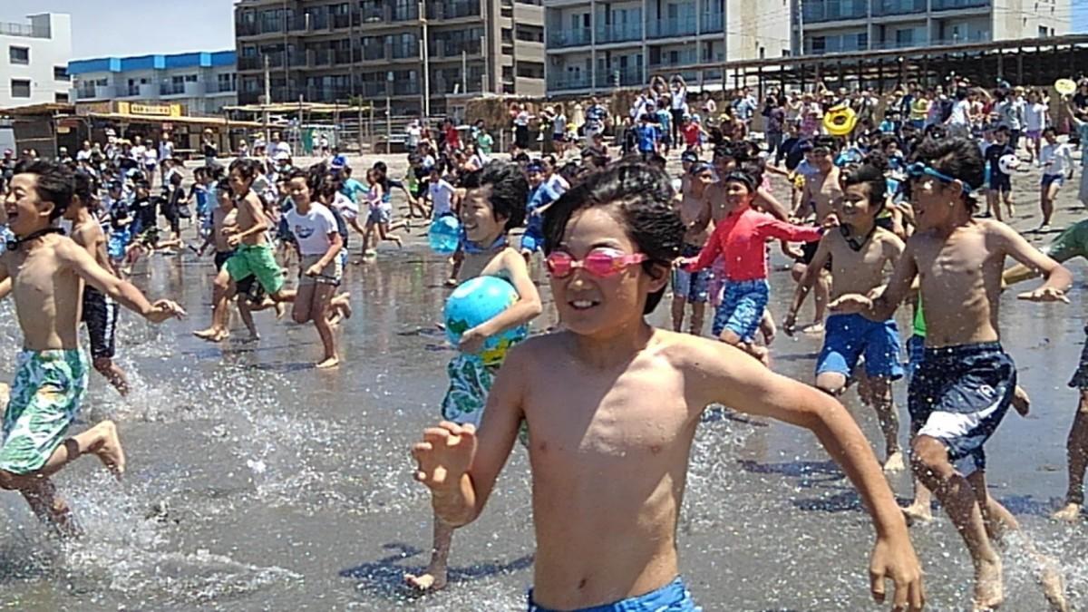 市長の海開きカウントダウンの合図のもと、一斉に海に入っていく地元小学生たち