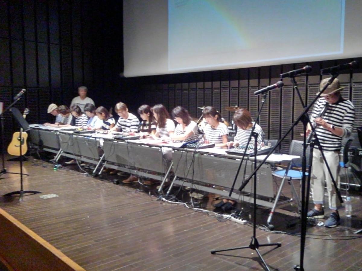逗子文化プラザホールで行われたコンサートで、iPadを使ってバンド演奏を披露するパソコン教室の先生たち