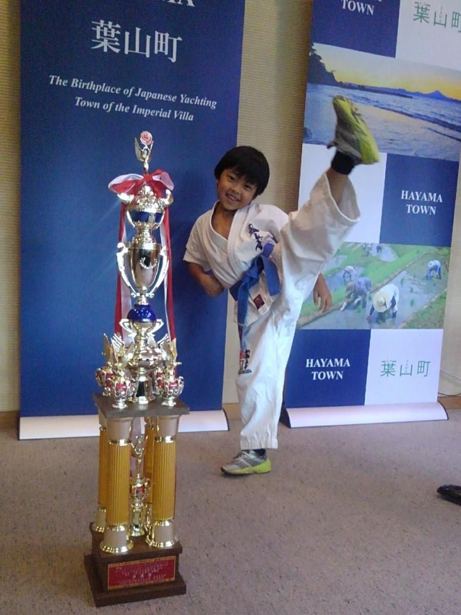 自分の背丈ほどもあるトロフィーを前に、得意の蹴りのポーズを披露する梶武蔵さん(葉山町役場町長室にて)