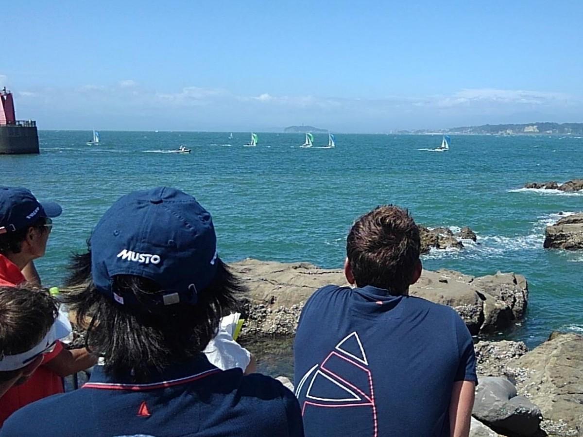 葉山港沖で行われたレースを観戦するブルーのオフィシャルシャツを着た英国チームメンバーたち。遠方に江ノ島