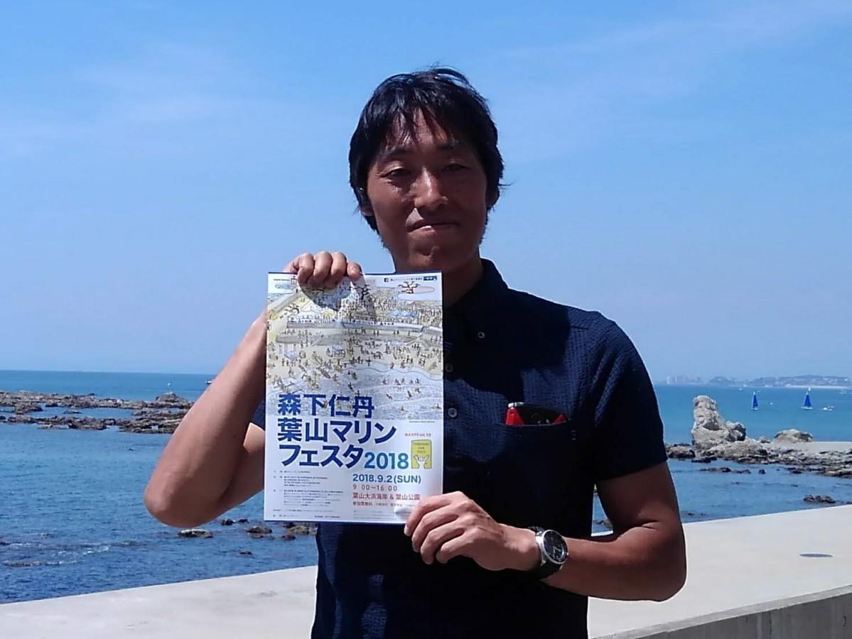 葉山マリンフェスタ実行委員会代表の佐久間泰介さん。手にしているチラシのイラストは父が描いた。「どういうイベントか」と聞かれたらこのイラストを見せれば済むという