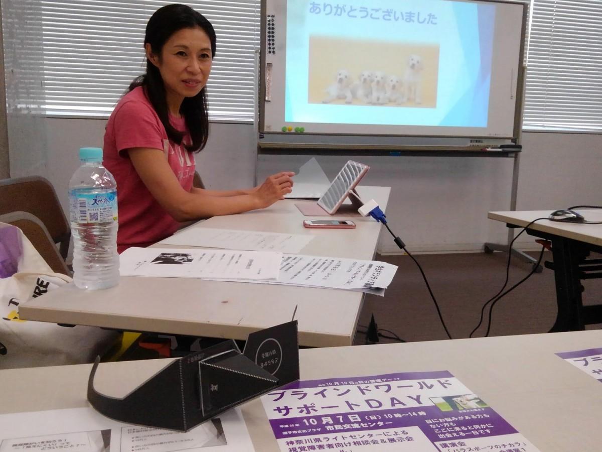 主催者の一人、眼科医の澤崎弘美さん。手前の黒い紙の眼鏡で見えにくさを体験できる