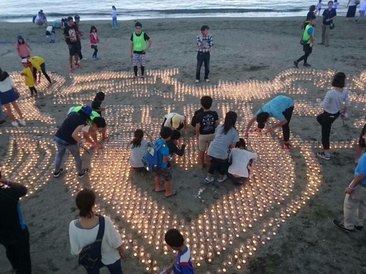 昨年の「Zushi Beach Candle」でキャンドルを並べた後、火をつけていく様子(提供=逗子葉山青年会議所)