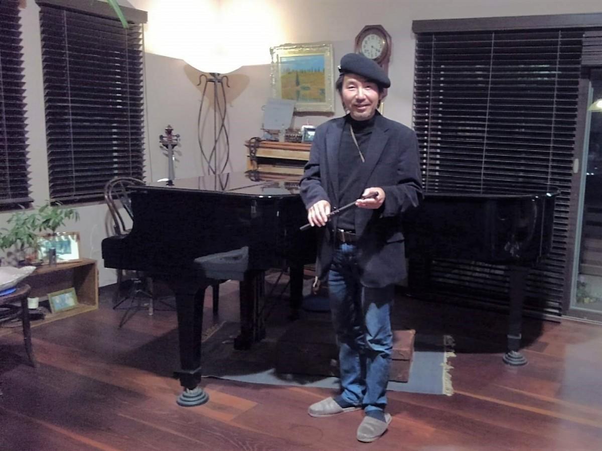 篠笛の村山二朗さん。「サロンみぎわ」のピアノの前で
