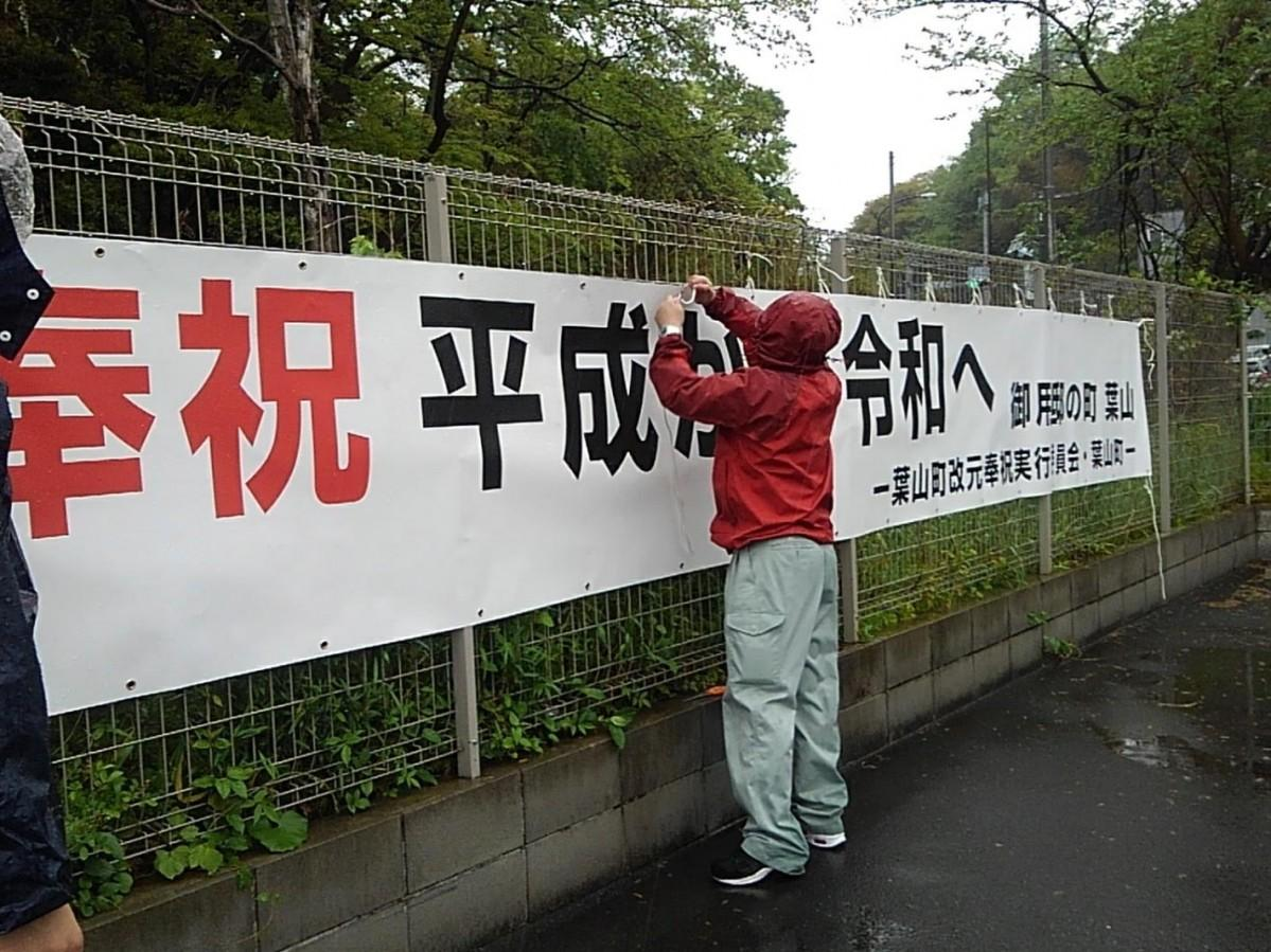 雨の中、行幸通りに面した「SHOPPING PLAZA HAYAMA STATION」の塀に横断幕を取り付ける職員