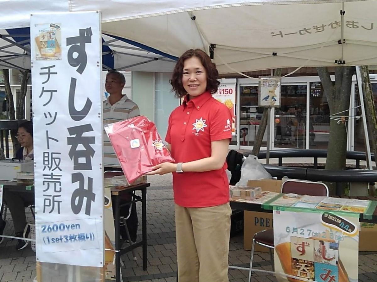 スペイン応援キャンペーンポロシャツを着用したオリンピック・パラリンピック担当の川嶋名津子さん。特設販売のブース前で