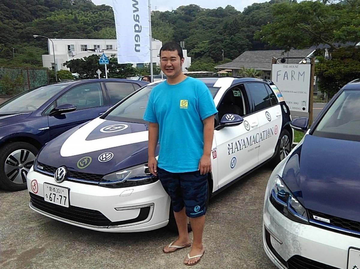 新しく拠点となった店のロゴ「〇(まる)げ」バージョンにラッピングされた車両と「げんべい」の社長、葉山さん